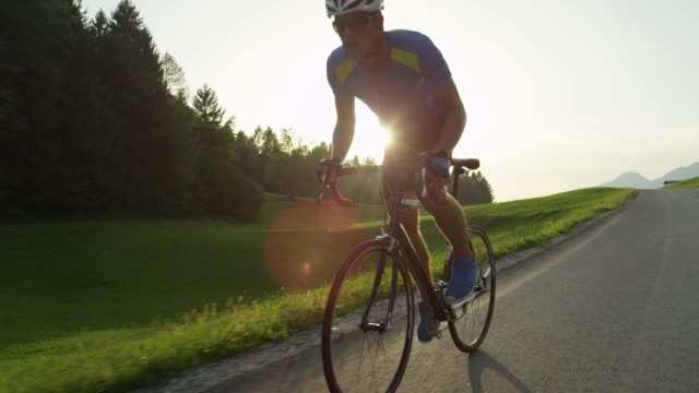 SLOW MOTION: Male biker pedals his road bicycle past the camera on sunny evening SLOW MOTION, LENS FLARE: Male biker pedals his road bicycle past the camera on a sunny evening. Young athlete riding his bike during race in the spring countryside. Pro cyclist easily overtakes camera biking stock videos & royalty-free footage