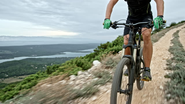 Male biker riding his mountain bike down a mountain ridge - video