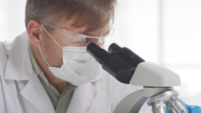 male biomedical scientist looking into microscope - covid testing filmów i materiałów b-roll