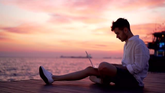 männer-blogger schreiben artikel durch das meer - junger mann stock-videos und b-roll-filmmaterial