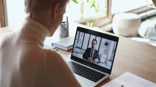 Male boss conference calling distance worker in corporate webcam videochat