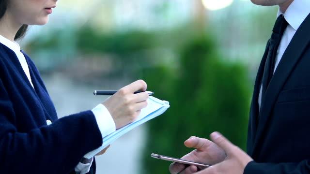 männlicher chef gibt anweisung an weibliche assistentin notizen machen, zeitplan planen - unterordnung stock-videos und b-roll-filmmaterial