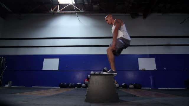 male box jump-front, low angle - bir orta yetişkin erkek sadece stok videoları ve detay görüntü çekimi