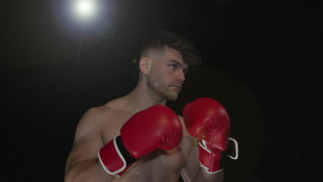 Male Boxer / boxing Portrait pose - Super Slow Motion 180 degree rotation Stock HD video clip footage of a male Boxer. Filmed in Super Slow motion, the camera rotates 180 degrees around the player. Black Background. Indoors. Boxing pre game stock videos & royalty-free footage