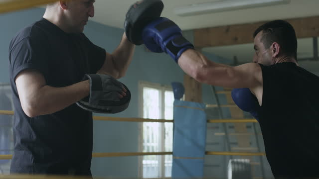 Male boxer practicing with his coach at gym video