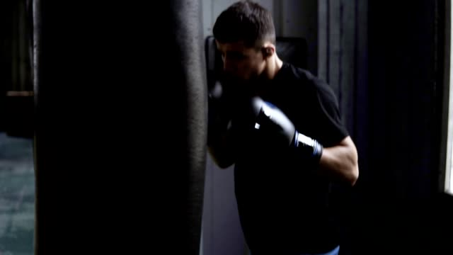Male boxer training. Doing strong, hard hits on boxing bag. Caucasian young guy workout at gym, hardworking, motivation