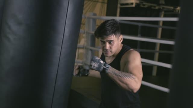 vídeos de stock e filmes b-roll de male boxer training in boxing club - campeão desportivo