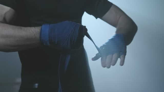 pugile maschio che avvolge le mani prima di combattere. giovane atleta che si prepara a combattere - pugno video stock e b–roll