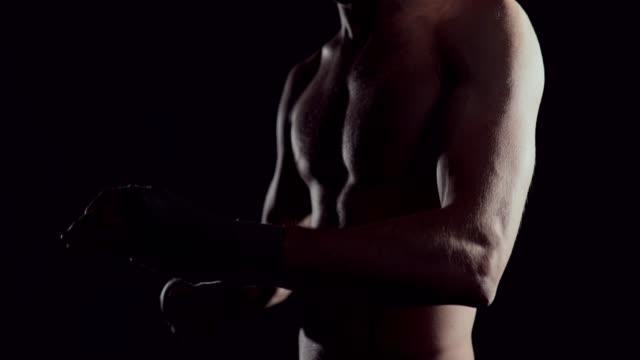 männlicher boxer wickelt seine hände mit handwrap. profi-boxer bandagen auf seiner hand wickeln. kämpfer, die umhüllung hände mit boxen wraps in der turnhalle - muskulös stock-videos und b-roll-filmmaterial