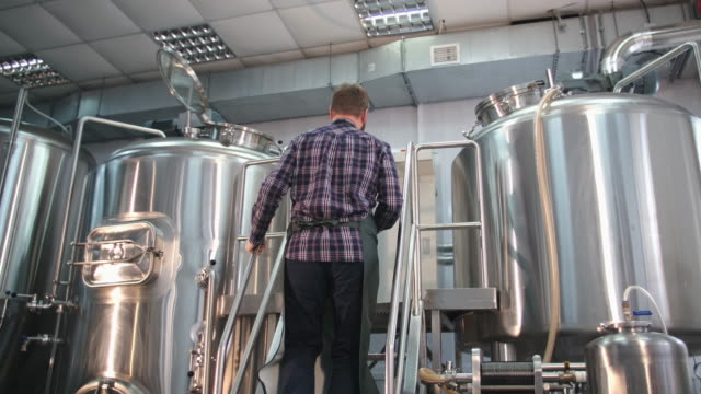A male brewer in an apron with a beard goes up the stairs to the beer tank, looks in and takes a reading Adult Male brewer in an apron with a beard climbs the stairs to the beer tank, looks inside and records storage tank stock videos & royalty-free footage
