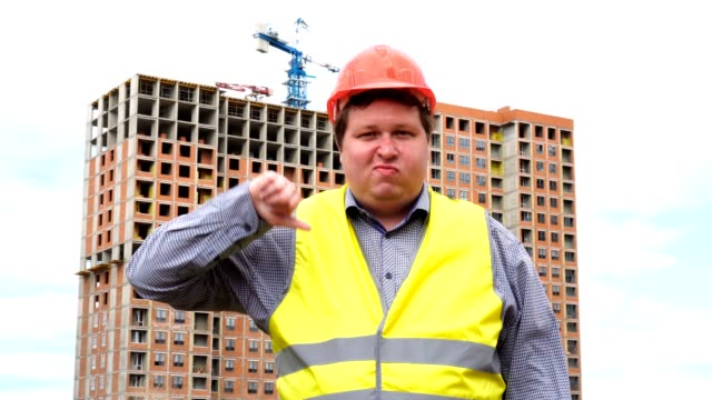 Male builder foreman, worker or architect on construction building site showing thumb down and looking to camera