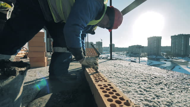 Male builder lays bricks in a row. Construction site, construction industry, construction worker concept. video