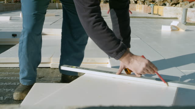 DS Male builder measuring expanded polystyrene foam for foundation insulation