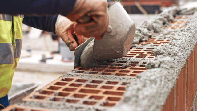 Male builder placing concrete on top of the bricks
