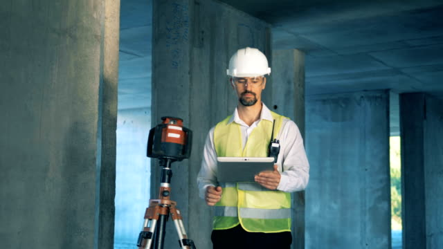 manliga byggnaden inspektör står nära lantmäteri enhet och arbetar på sin tablett - topografi bildbanksvideor och videomaterial från bakom kulisserna