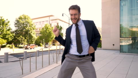 Male business executive crazy victory dancing his success and achievement Handsome male business executive with a beard silly victory dancing his success and achievement in slow motion outside his office building pride stock videos & royalty-free footage