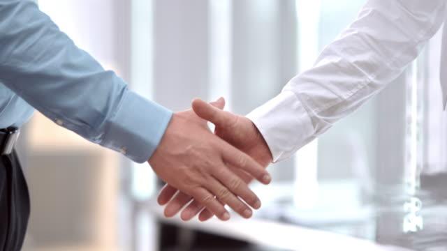slo, mo, pan männliche business handshake - abmachung stock-videos und b-roll-filmmaterial