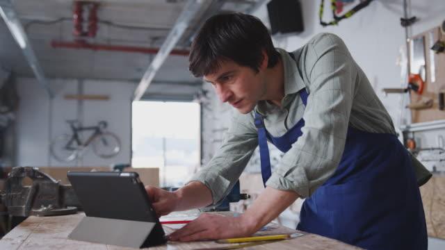 männlicher geschäftsinhaber in werkstatt für den bau von fahrrädern mit digitaler tablet - werkstatt stock-videos und b-roll-filmmaterial