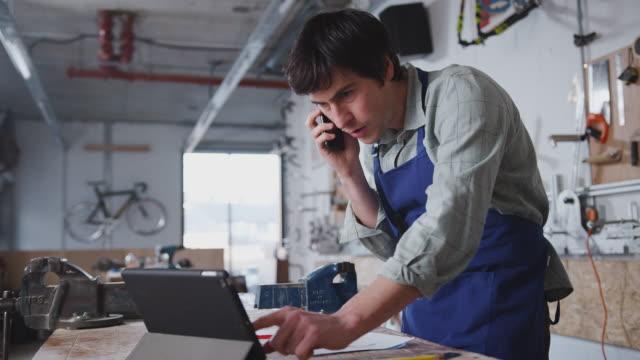 manlig företagare i verkstad med digital surfplatta och ringa samtal på mobiltelefon - småföretagande bildbanksvideor och videomaterial från bakom kulisserna
