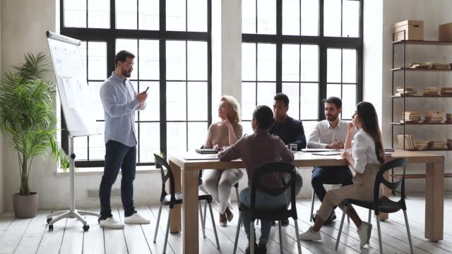 vídeos de stock, filmes e b-roll de o instrutor de negócio masculino comunica-se com o grupo de negócio durante a oficina - rh