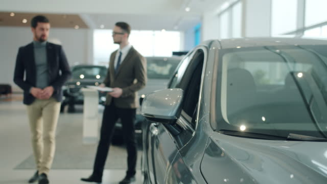 Male buyer choosing brand new car in showroom discussing deal with manager. Focus on vehicle mirror video