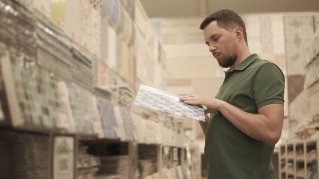 male buyer is inspecting product catalog of tile for finishing works in houses - piastrella video stock e b–roll