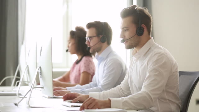 Male call center agent wear wireless headset consulting customer Male call center agent wear wireless headset consulting online customer solving complaint use computer, business man operator talking working in service helpline support office with professional team promotion employment stock videos & royalty-free footage