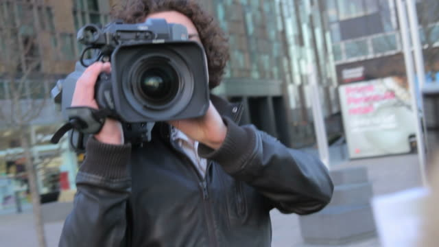 Male camera opperator and female presenter on location broadcasting video