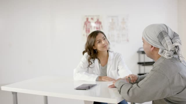 Male Cancer Patient in Consultation with Female Medical Professional A male cancer patient wearing a scarf on his head meets with a specialist to discuss different treatment plans. oncology stock videos & royalty-free footage