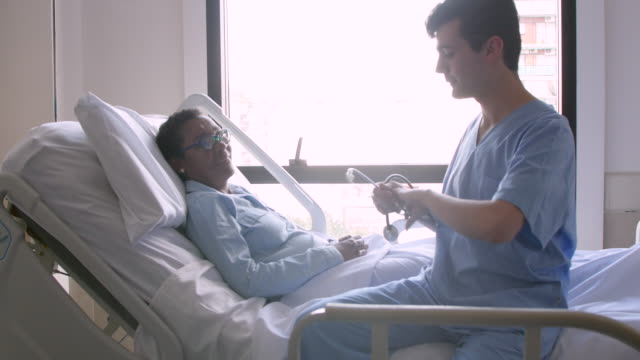 Male cardiologist talking to his patient while she is lying down on hospital bed and then using his stethoscope