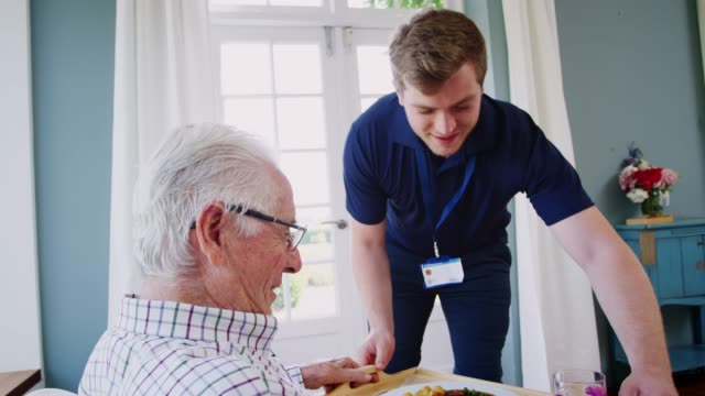 male care worker serving dinner to a senior man at his home - senior care stock videos and b-roll footage