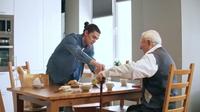 stockvideo's en b-roll-footage met mannelijke caregiver serveren van het ontbijt tot senior man - gezondheidszorg beroep