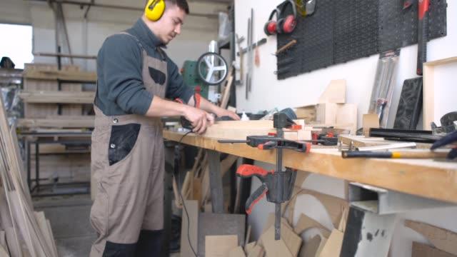 Male carpenter assembling wooden item