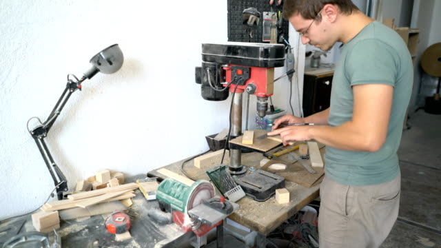 Male carpenter drilling wooden parts in his workshop video
