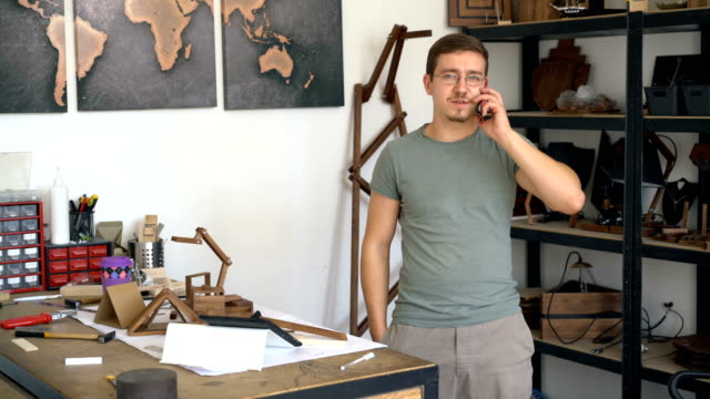Male carpenter standing next to the work table and talking on the phone. video