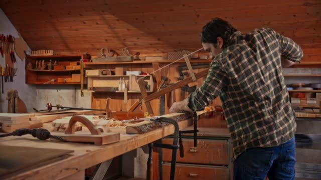 Male carpenter using a frame saw to cut a board in his shop
