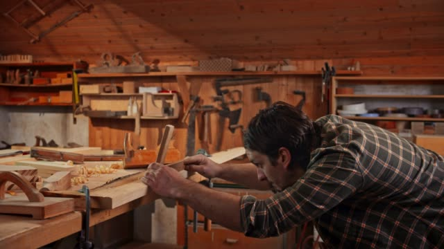 Male carpenter using a plane to square a board in his shop