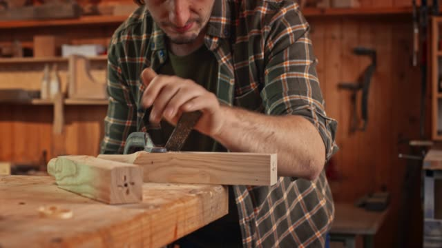 Male carpenter using a rasp to shape a part of his workpiece
