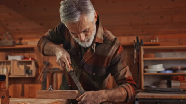 Male carpenter with a grey beard and hair using a file to finish a part of workpiece in his workshop