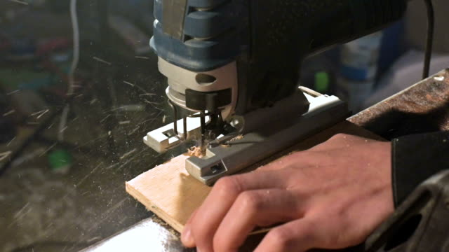 Male carpenter's hands works as an electric jigsaw in his home workshop. Cutting wooden parts in slow motion Male carpenter's hands works as an electric jigsaw in his home workshop. Cutting wooden parts in slow motion. handbook stock videos & royalty-free footage