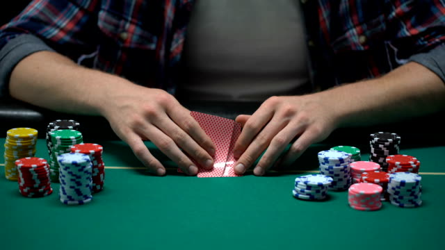 Male casino player checking card combination and betting all chips, strategy
