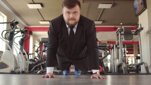 A male caucasian businessman in a black suit performs physical exercises in a gym, wring out of the floor and looks into the camera as a concept of a healthy lifestyle office workers A male caucasian businessman in a black suit performs physical exercises in a gym, wring out of the floor and looks into the camera as a concept of a healthy lifestyle office workers, sports center push ups stock videos & royalty-free footage