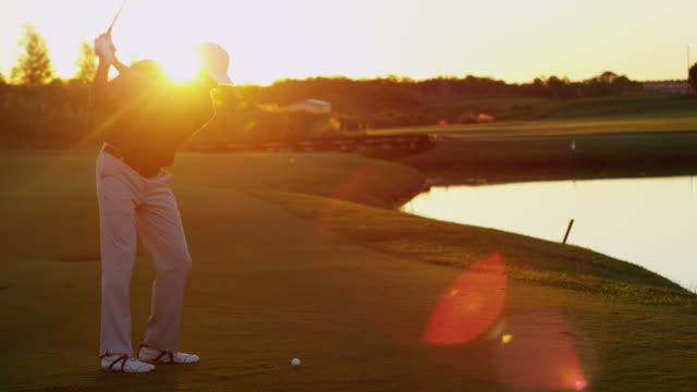 夕暮れ時の彼のスイングを練習して男性の白人ゴルファー - ゴルフ点の映像素材/bロール