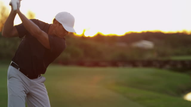 Male Caucasian golfer practicing his swing at sunset