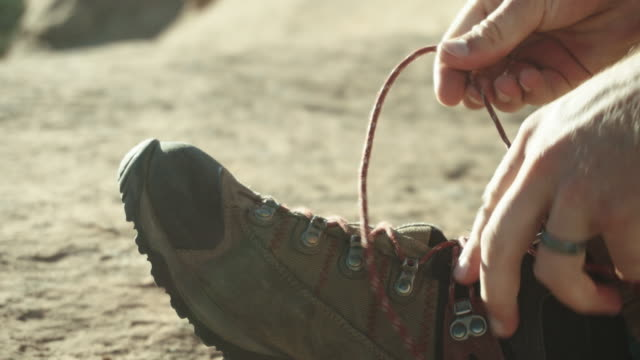 vídeos de stock e filmes b-roll de male caucasian hiker ties his shoes - bota