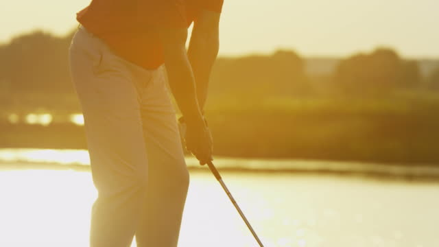 Male Caucasian professional golfer teeing off at sunrise video
