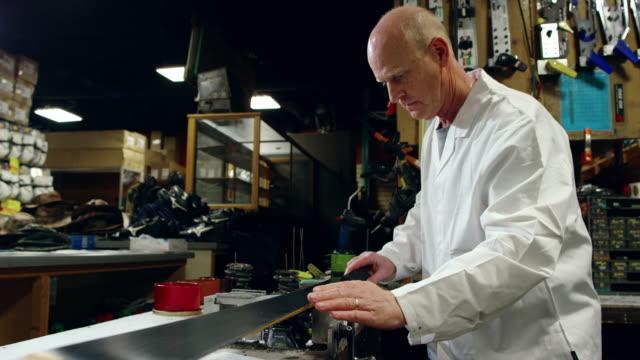 a male caucasian ski technician in his fifties checks the base flatness level of a downhill ski in an indoor repair shop - negozio sci video stock e b–roll