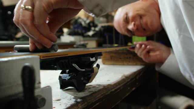 a male caucasian ski technician in his fifties checks the base flatness level of a downhill ski in an indoor repair shop - sprzęt sportowy filmów i materiałów b-roll