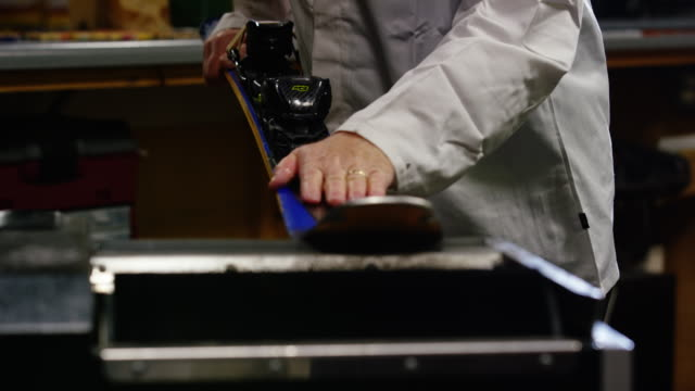 a male caucasian ski technician in his fifties picks up and inspects a downhill ski and then uses a belt grinder to smooth the bottom of a downhill ski in an indoor repair shop - negozio sci video stock e b–roll
