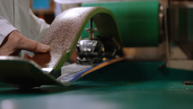 a male caucasian ski technician in his fifties uses a wet grinder to smooth the bottom of a downhill ski in an indoor repair shop - negozio sci video stock e b–roll